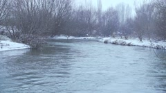 Snow falls over the river in slow motion.mp4 Stock Footage