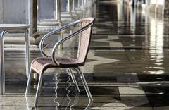chair at high tide under the arcades during the flood in Venice - stock photo