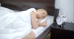 Pretty Sleeping Woman with Alarm Clock Next to Her - stock footage