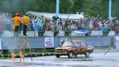 Two stuntmen performing at car stunt show, crowd cheering loudly Stock Footage