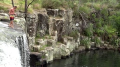 Man jumps off charlies rock waterfall kerikeri northland new zealand 01 Stock Footage