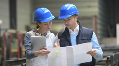 Engineers in factory reading blueprint Stock Footage
