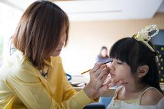 Professional makeup artist working with cute asian child Stock Photos