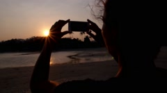 Silhouette of Woman Taking Picture of Sunset with Phone at Beach Stock Footage