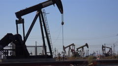 Wide shot of many oil derricks pumping in an oilfield. Stock Footage