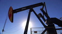 Low angle of oil derrick pumping against blue sky. Stock Footage