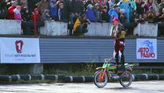 Stunt person plays accordion while standing on moving motorcycle Stock Footage
