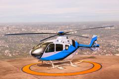 helicopter parking on building roof top use for commercial air transportation - stock photo