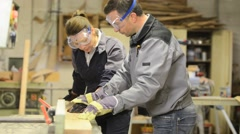 Instructor showing trainee how to use sawing machine - stock footage