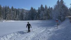Aerial - Man walking away from the snowy field, then rising above the glade Stock Footage