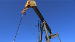 Low angle view in an oilfield of an oil derrick pumping. Stock Footage