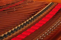 Piano strings with red felt. Stock Photos