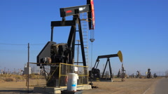 Oil derricks pump crude in an oilfield. Stock Footage