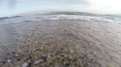 Sea waves, the camera at the sand, the water coming into the lens. Stock Footage