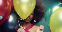 Beautiful young hispanic woman dancing celebrating birthday multicolored balloon Arkistovideo