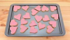 Array of heart-shaped cookies with pink frosting Stock Photos