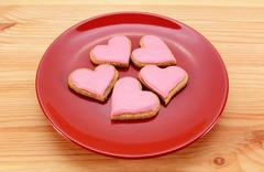 Five heart-shaped iced cookies on a red plate - stock photo