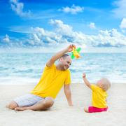 Baby and father playing toy plane - stock photo