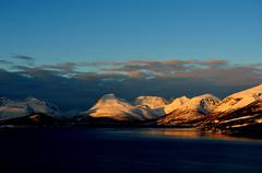 Snowy mountain peaks and blue fjord water in the arctic circle winter Stock Photos