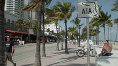 A1A tourist area in Fort Lauderdale, pan to ocean Stock Footage