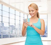 Smiling woman with smartphone in gym Kuvituskuvat