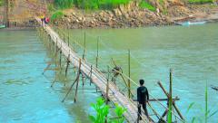 LUANG PRABANG, LAOS - CIRCA DEC 2013: Handmade bamboo bridge provides access Stock Footage