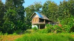 LUANG PRABANG, LAOS - CIRCA DEC 2013: Wooden house on stilts on a farm near L Stock Footage