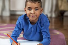 Young mixed race boy drawing on paper with crayon. Stock Photos