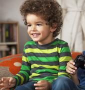 Young boy playing video game, at home. Stock Photos