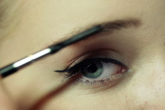 Close up of cosmetician brushing young woman's eyebrows at beauty salon NTSC Stock Footage