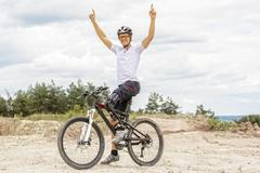Handicapped mountain bike raising up arms Stock Photos
