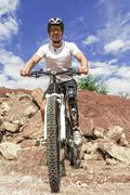 Handicapped mountain bike rider between rocks - stock photo