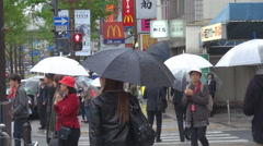 Busy sidewalk Osaka city pedestrian people cross zebra umbrella rainy day iconic Stock Footage