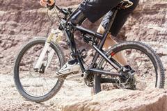 Handicapped mountain bike rider between rocks - stock photo