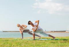 Smiling couple making yoga exercises outdoors Kuvituskuvat