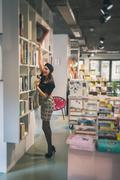 Stock Photo of Beautiful young brunette posing in a bookstore