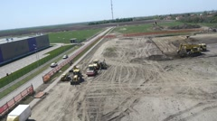 Aerial view on heavy machines preparing ground for new factory foundation Stock Footage