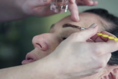 Stock Video Footage of Young woman getting eyebrow makeup at beauty salon NTSC