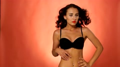 Sensual, young, brunette woman looking at camera in black bra on vinous Stock Footage