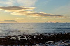 Vibrant snowy sea shore on sunny day with beautiful mountain range in horizon Stock Photos