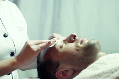 Cosmetician cleaning man's face with cotton pads at beauty salon NTSC Stock Footage