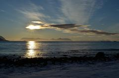 Vibrant snowy sea shore on sunny day with beautiful mountain range in horizon - stock photo
