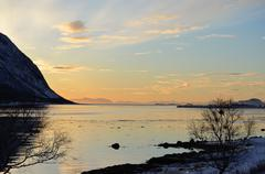 serene landscape with fjord and vibrant coloured sky - stock photo