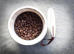 Coffee beans in wooden bowl - stock photo