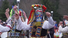 Mummers festival in Bulgaria mens with colorful masks  jump in slow motion Stock Footage