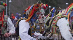 Mummers festival in Bulgaria men with colorful masks and bells jump Stock Footage