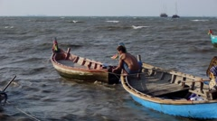 Man works with tackles Longtail boat in a storm, balancing, strong waves, sunny Stock Footage