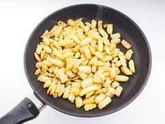 Frying chopped potatoes in a fry pan Stock Photos