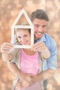 Composite image of young couple hugging and holding house outline - stock photo