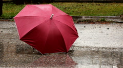 Red umbrella on the wet ground on rainy day Stock Footage